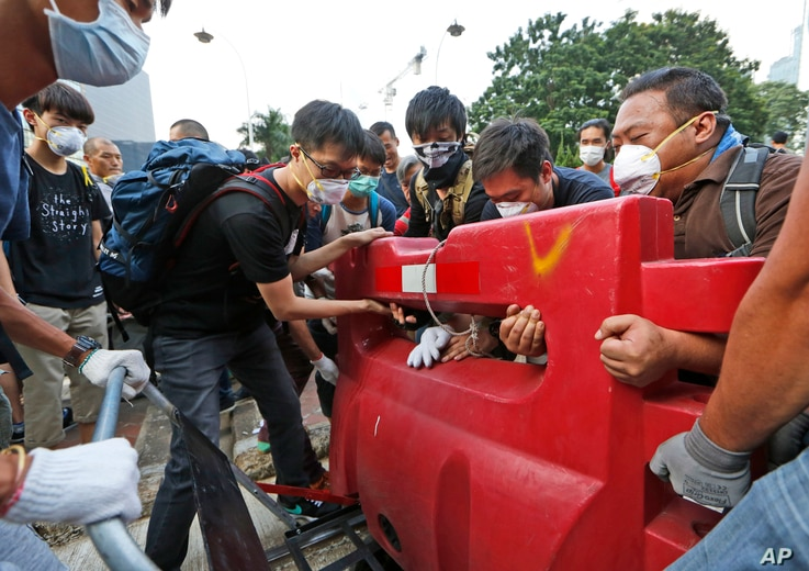 Pro-democracy protesters build a barricade on the main road in the occupied areas outside the government headquarters in Hong Kong's Admiralty, Monday, Oct. 13, 2014. Officers took away unmanned metal barricades at the edges of the city's Central fin...