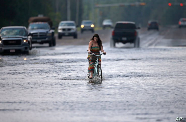 Cara Crawford, turns around after trying to ride her bike through high water to get to Sunday services at a nearby church, in the aftermath of Tropical Storm Harvey in Vidor, Texas, Sunday, Sept. 3, 2017.