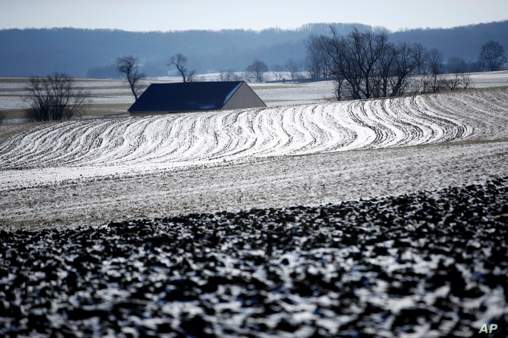 The sun reflects off of snow and ice on a farmer's frozen field in Ronks, Pennsylvania, Jan. 2, 2018.