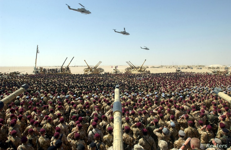 British troops gather for a briefing by US Lieutenant General Jeff Conway, Commanding General 1st Marine Expeditionary Force, in the Kuwait desert, March 14, 2003.