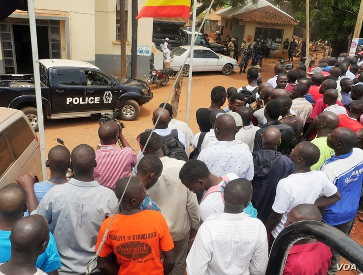 Protesters line up in front of Kira Road Police Station where opposition candidate Kizza Besigye was detained while campaigning for president, Kampala, Feb. 15, 2016. (E. Paula/VOA)