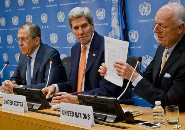 U.N. Special Envoy for Syria Staffan de Mistura, right, shows a copy of a Security Council resolution concerning Syria, during a press conference with Russian Foreign Minister Sergei Lavrov, left, and U.S. Secretary of State John Kerry  at U.N. headq...