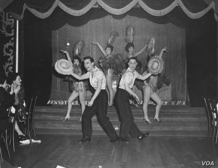 """Jimmy """"Jay"""" Borges, left, and Tony Wing in performance at Forbidden City; Wing's sister, Arlene, is seen above his head; Sisko Borges, Jimmy Jay's then-wife, is behind Jay, to the right, 1959 (Courtesy DeepFocus Productions, Inc.)."""