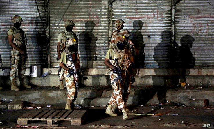 Pakistani paramilitary troops take up positions during a gunbattle with militants in Karachi, Pakistan, April 25, 2017.