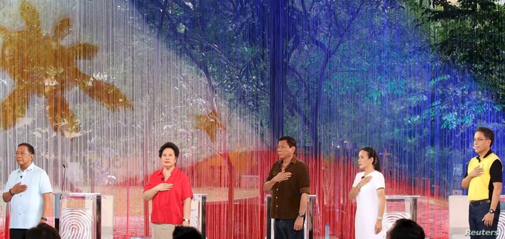 Philippine Presidential candidates sing the national anthem before the start of a April 24, 2016 presidential debate in Dagupan City.