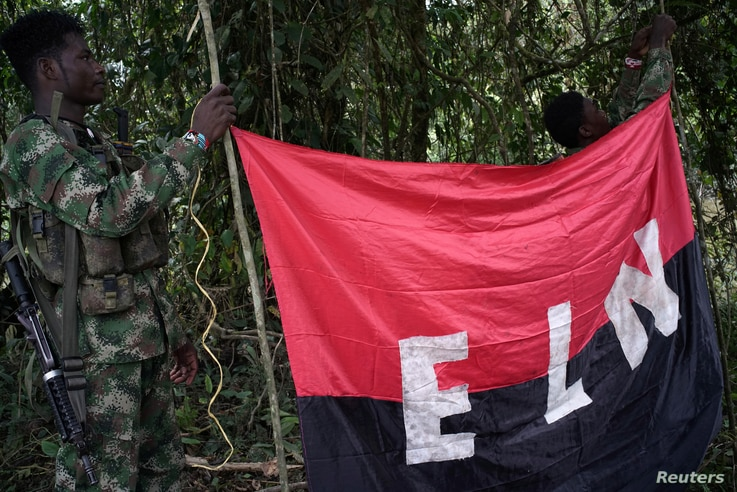 Rebels of the National Liberation Army hold a banner in the northwestern jungles in Colombia, Aug. 30, 2017.