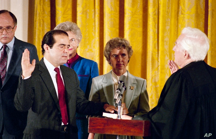 Retiring Chief Justice Warren Burger, right, administers an oath to Antonin Scalia, as Scalia's wife Maureen holds the bible in the East Room of White House, Sept. 26, 1986.
