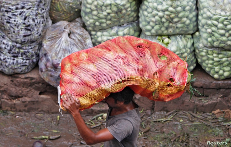 FILE - A man carries a sack filled with maize at a wholesale vegetable market in the western Indian city of Ahmedabad, Aug. 14, 2012.