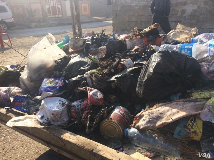 In the relative safety of Mosul neighborhoods where IS fled weeks or months ago, trash piles build up and locals say their immediate concern is now health issues from the increasing pollution, Jan. 9, 2017. (H. Murdock/VOA)