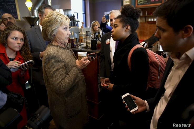 FILE - U.S. Democratic presidential candidate Hillary Clinton has an exchange with a young woman asking questions about issues pertaining to the Somali-American community as she greets people at Mapps Coffee in Minneapolis, Minnesota, March 1, 2016. ...