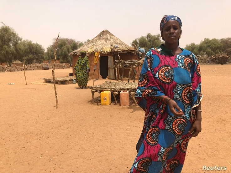 A woman stands in front of her mud-brick hut in Mafoundou village, Gorgol region, Mauritania, March 30, 2018.