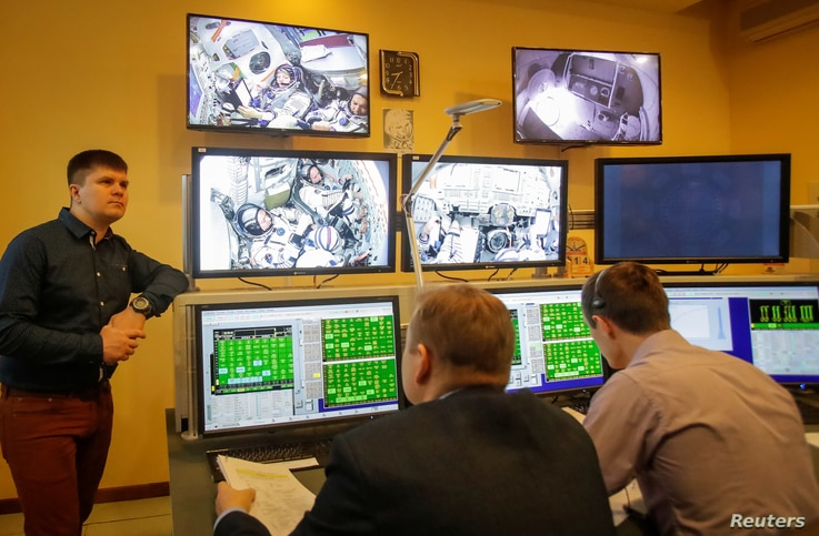 Specialists watch broadcasts from the Soyuz spacecraft showing astronaut David Saint-Jacques of Canada, Oleg Kononenko of Russia and astronaut Anne McClain of the U.S. attending the final qualification training for their upcoming space mission in Sta...