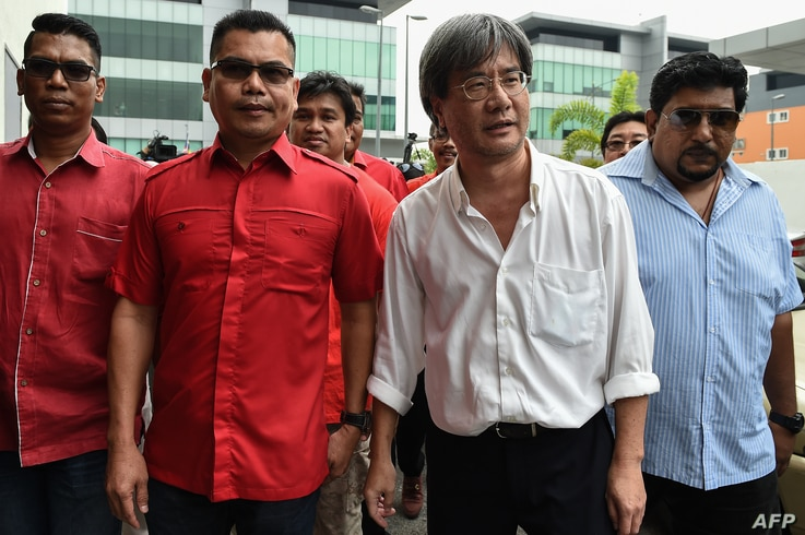 This picture taken on November 3, 2016 shows Jamal Yunos (2nd L), a division head member of the ruling United Malays National Organisation (UMNO) party, walking with Malaysiakini's editor-in-chief Steven Gan (2nd R) before their press conference in P...