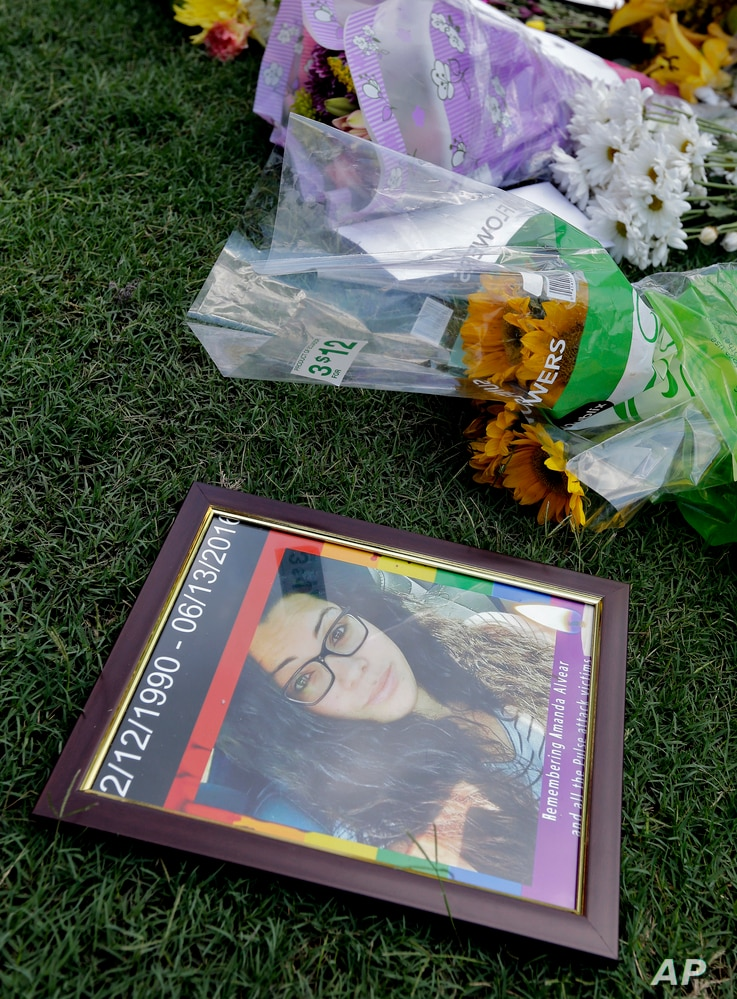 A photo of Amanda Alvear, one of the victims in the fatal shooting at the Pulse Orlando nightclub, lies at a makeshift memorial in Orlando, Fla., June 13, 2016.