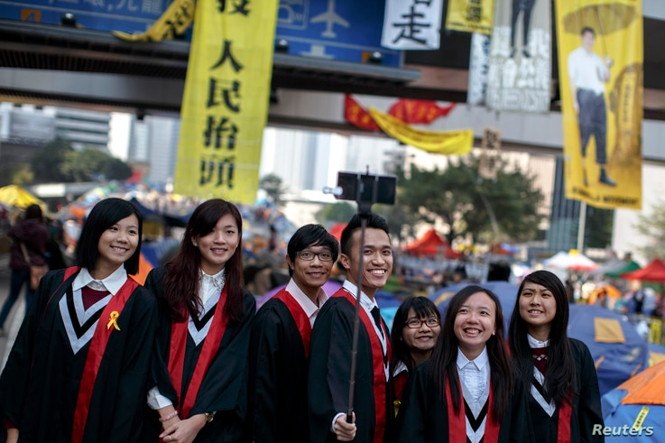 Graduate students have their picture taken at an Occupy Central protest site outside the government headquarters at Admiralty in Hong Kong, Dec. 9, 2014.