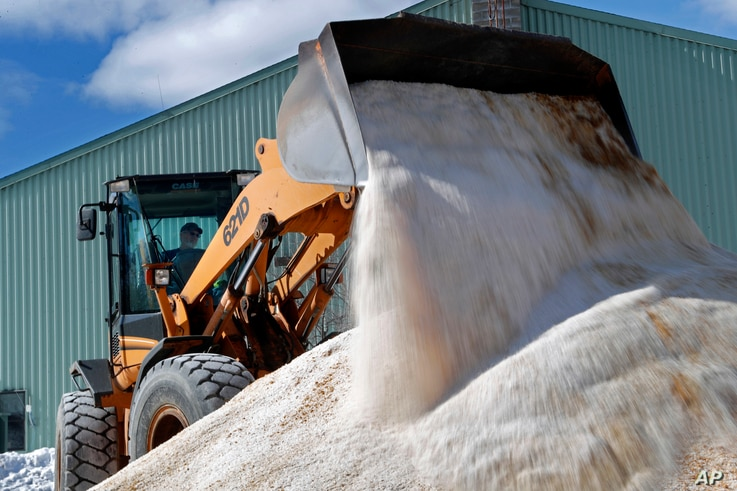 David Osgood, crew leader of the public works department, mixes road salt, March 12, 2018, in Freeport, Maine.