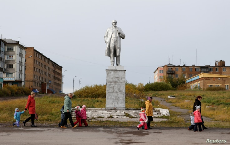 FILE - Pupils of a local nursery school and adults walk past a monument to Soviet state founder Vladimir Lenin in Vorgashor settlement outside the far northern city of Vorkuta, Russia, Sept. 17, 2018.