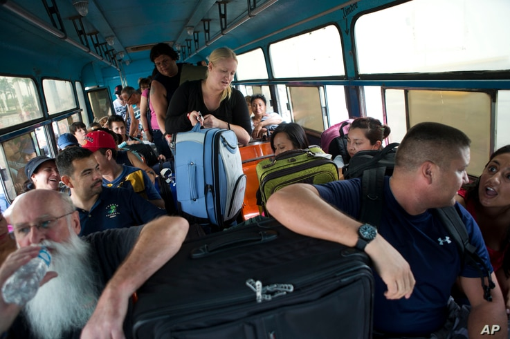 Mexican and international tourists board a bus to be transported to a shelter, bracing for the arrival of Hurricane Patricia, in Puerto Vallarta, Mexico, Oct. 23, 2015.