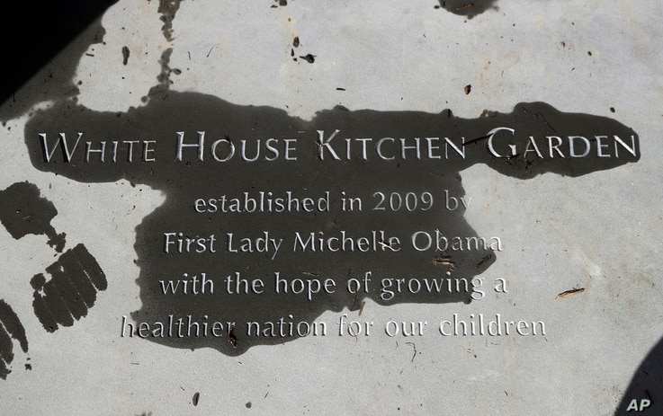"""A new paver etched with markings """"White House Kitchen Garden"""" is seen at the entrance to the White House Kitchen Garden at the White House in Washington, Oct. 5, 2016."""