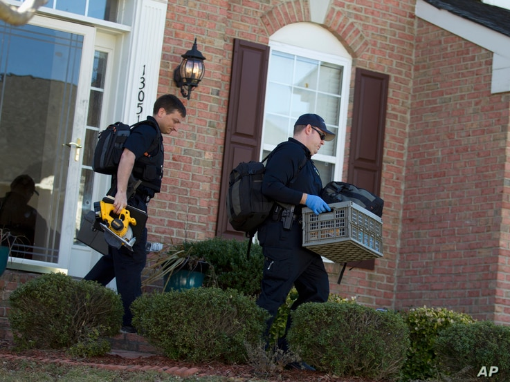 FILE - Prince William County, Va., Crime Scene Unit officers collect evidence at the house Ronald Williams Hamilton in Woodbridge, Va., Feb. 29, 2016, following a fatal shooting at the residence, during a domestic dispute. Hamilton later faced charge...