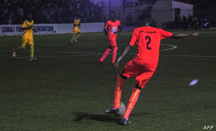 Football players from Hodan district (orange) and Waberi district (yellow) play in the first nighttime game in 30 years in Modadishu, Somalia, Sept. 8, 2017.