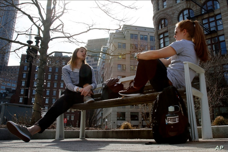 FILE - Sydney Dollmeyer (left) and Emily Daly enjoy lunch in the sun along the Rose Kennedy Greenway, Feb. 24, 2017, on the warmest February day ever recorded in Boston.