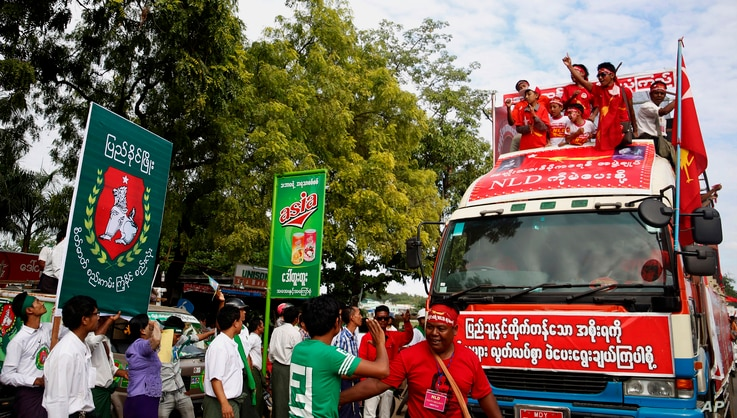 Supporters of Myanmar's opposition leader Aung San Suu Kyi's National League for Democracy party, on the party's campaign truck, right, pass an office of the rival Union Solidarity and Development Party (USDP) in Meiktila, Mandalay Region, Myanmar, N...
