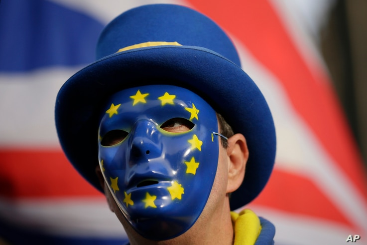 An anti-Brexit demonstrator wears a mask bearing the stars of the European flag, during a protest outside the houses of Parliament, in London,  Dec. 19, 2018.