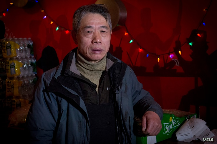 """Aimin Liu, 59, says he is able to continue delivering meals because of his e-bike. """"My legs are no good,"""" he tells VOA. """"I'm not capable of riding a regular bike."""""""