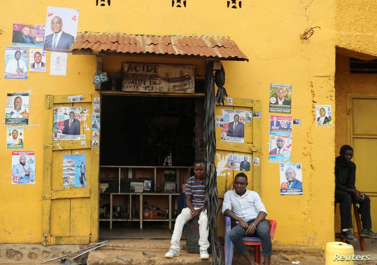 Men sit in front of election posters in Beni, North Kivu Province of Democratic Republic of Congo, Dec. 5, 2018.