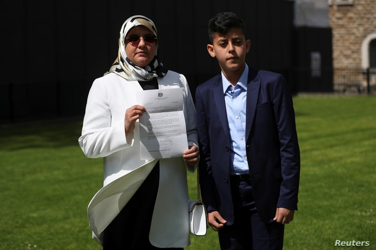 Fatima Boudchar, wife of Libyan dissident Abdel Hakim Belhaj, stands with their son Abderrahim, as she holds a letter of apology from British Prime Minister Theresa May outside the Houses of Parliament in Westminster, London, Britain, May 10, 2018.