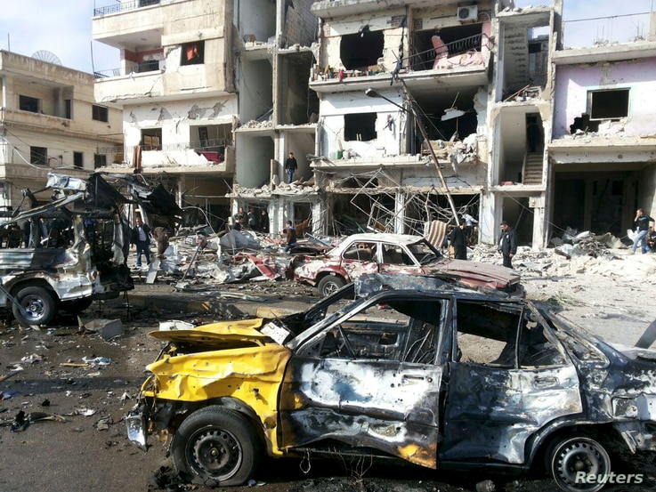 People inspect the site of a two bomb blasts in the government-controlled city of Homs, Syria, in this handout picture provided by SANA on February 21, 2016.