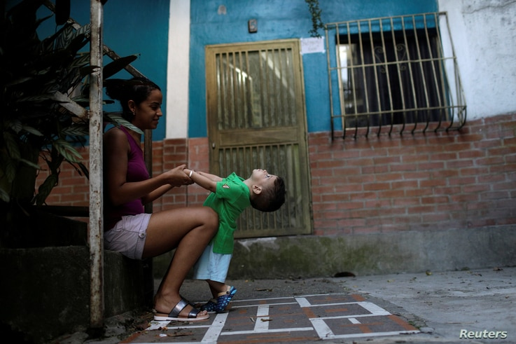 """Veruska Torres plays with her son on the outskirts of Caracas, Venezuela, October 11, 2017. He is wearing a new t-shirt bought with prize money won on """"Los Animalitos"""" (or the Little Animals) betting game."""