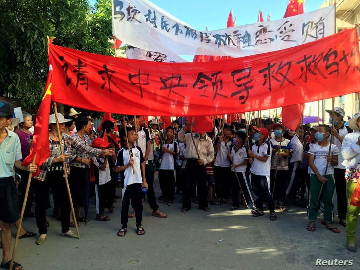 """Villagers carry banners which read """"Plead the central government to help Wukan"""" (in red) and """"Wukan villagers don't believe Lin Zuluan took bribes"""" during a protest in Wukan, China's Guangdong province on June 22, 2016."""