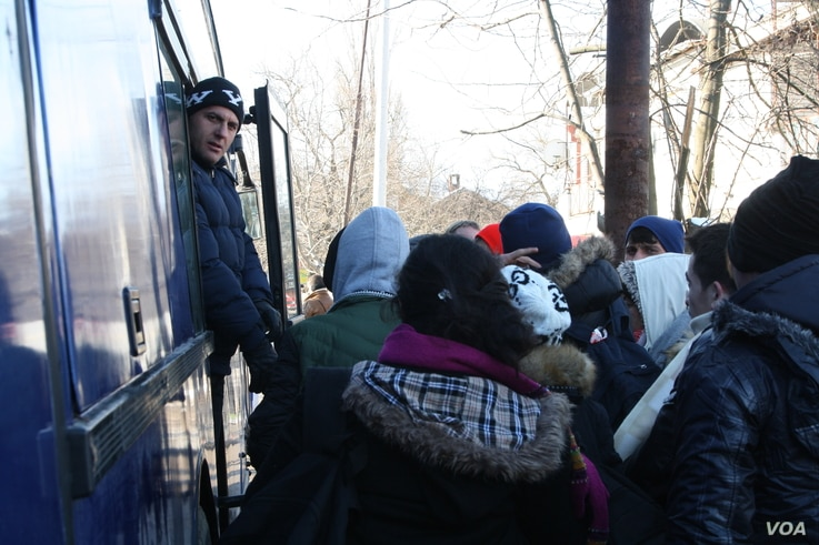 Refugees board a bus to leave Presevo for Serbia's northern border with Croatia, Jan. 19, 2016. (P. Walter Wellman/VOA)