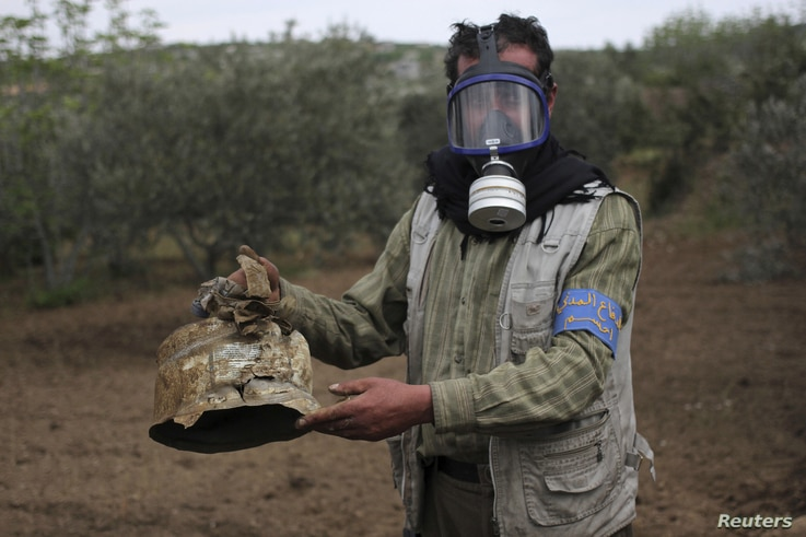 A Civil Defense member carries a damaged canister in Ibleen village from what activists said was a chlorine gas attack, on Kansafra, Ibleen and Josef villages in Syria May 3, 2015.