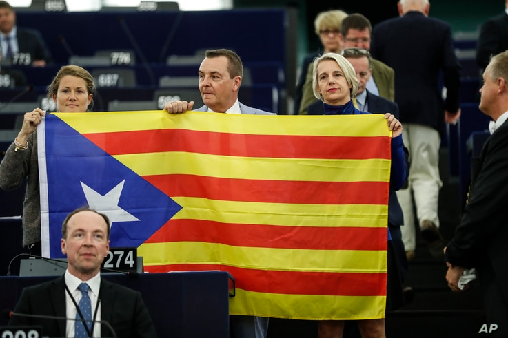 Belgium members of the European Parliament, Anneleen Van Bossuyt, left, Mark Demesmaeker and Helga Stevens, right, display a Catalan flag in support of the disputed independence vote Sunday in Catalonia during a session at the European Parliament in ...