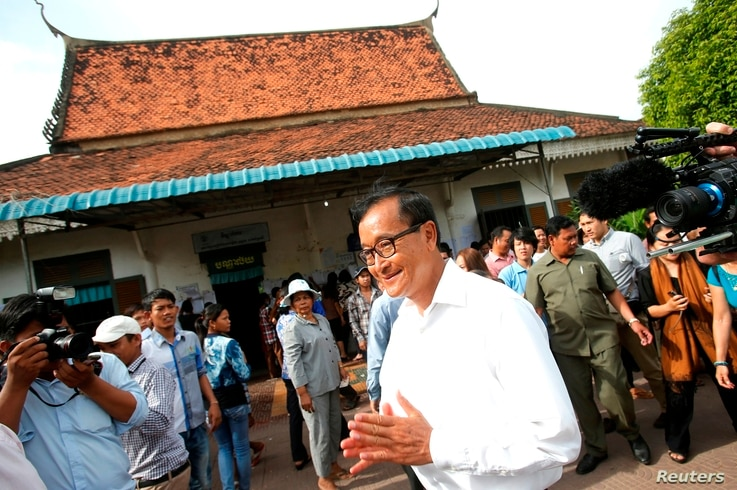 Sam Rainsy, president of the Cambodia National Rescue Party (CNRP), visits a polling station during the general elections in Phnom Penh, July 28, 2013.