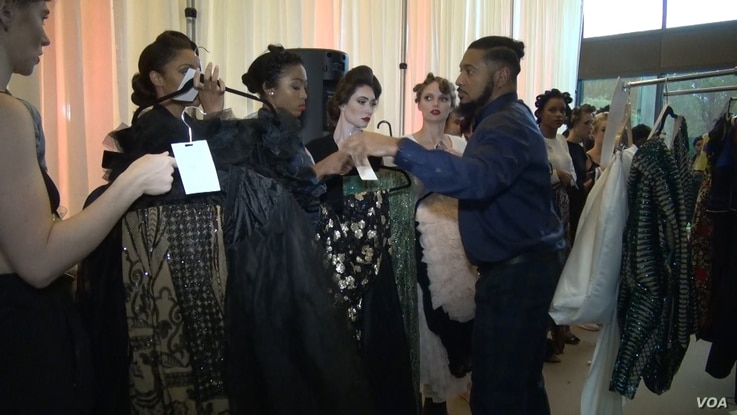 DC Fashion Week Founder Ean Williams works with models who are about to take the runway. (Photo: J. Soh / VOA )