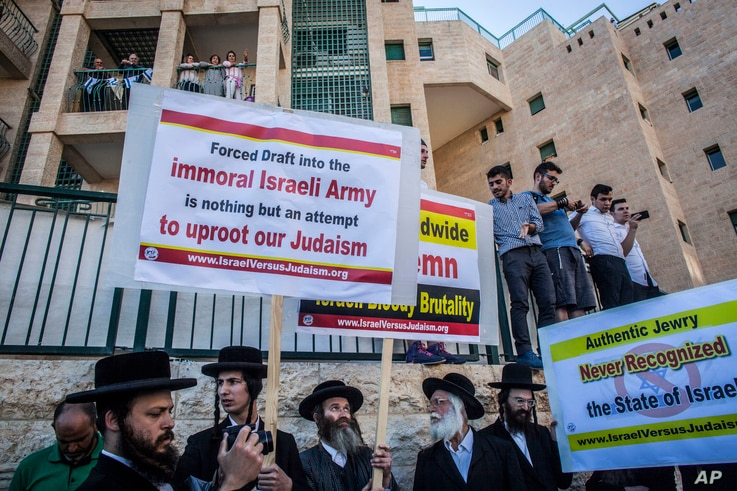 FILE - Ultra-Orthodox Jewish men wave signs, some protesting the draft, and chant outside the new U.S. Embassy in Jerusalem, May 14, 2018.