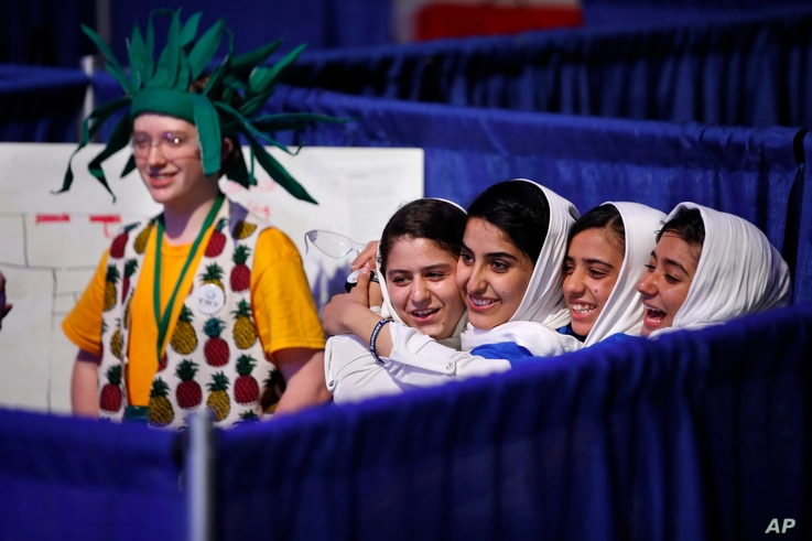 Team Afghanistan, from second from left, Kawsar Rashan, Lida Azizi, Somayeh Faruqi,and Rodaba Noori, next to a member of Team Australia, at left, hug before their final round of competition at the FIRST Global Robotics Challenge, July 18, 2017, in Wa...
