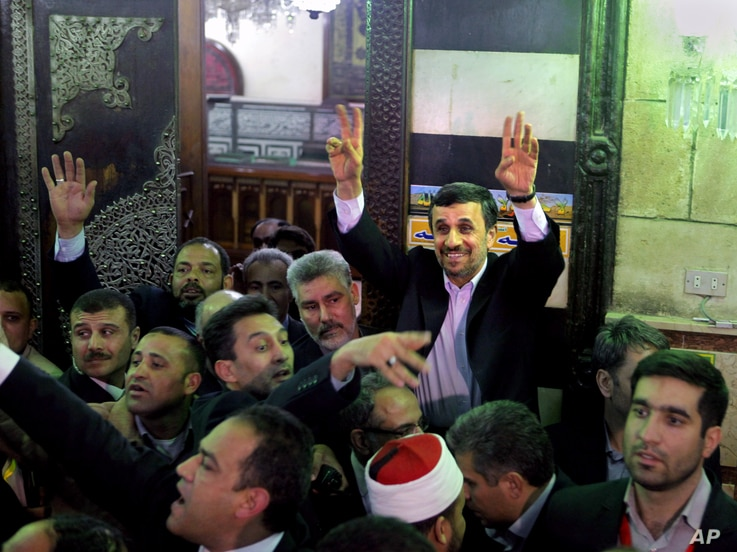 Iran's President Mahmoud Ahmadinejad waves to Egyptian worshippers after he visits the shrine of Imam Hussein, the grandson of Islam's Prophet Mohammad, in Cairo, Egypt, February 5, 2013.