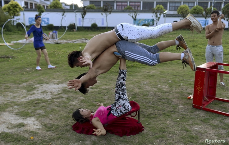 A woman (bottom) balances two men with her feet as students practice at an acrobatic school in Sanwang village, Anhui province, China, July 30, 2015. With a population of 1.37 billion, China has more men than women. The current ratio is at about 105:...