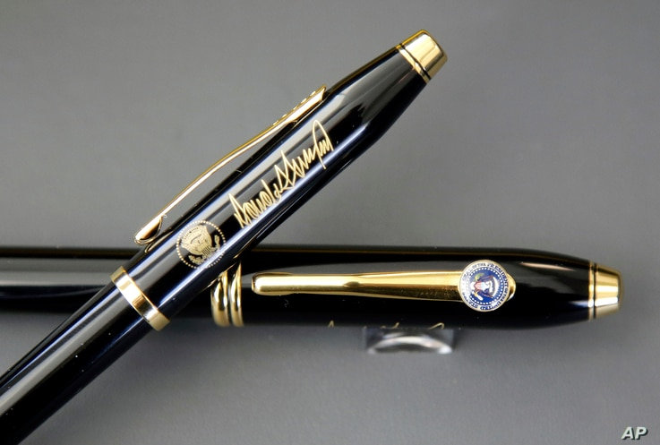 A.T. Cross Co. custom-made pens, designed for President Donald Trump, featuring his signature and presidential seals, are displayed at the Cross Company Store in Providence, R.I. Trump chose the Cross Century II model, top, for deliveries to the Whit...