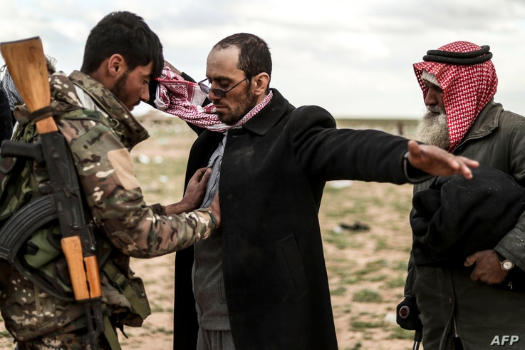 Men suspected of being Islamic State are searched by a member of the Kurdish-led Syrian Democratic Forces (SDF) after leaving the IS group's last holdout of Baghuz, in Syria's northern Deir Ezzor province, Feb. 27, 2019.