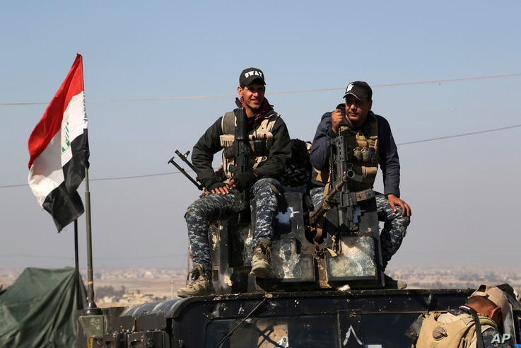 Two policemen sit atop of their armored vehicle as Iraqi federal police deploy after regaining control of the town of Abu Saif, west of Mosul, Iraq, Feb. 22, 2017.
