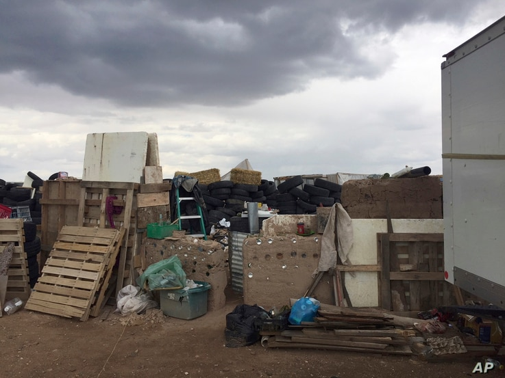 This Friday, Aug. 3, 2018, photo released by Taos County Sheriff's Office shows a rural compound during a search for a missing 3-year-old boy in Amalia, N.M.