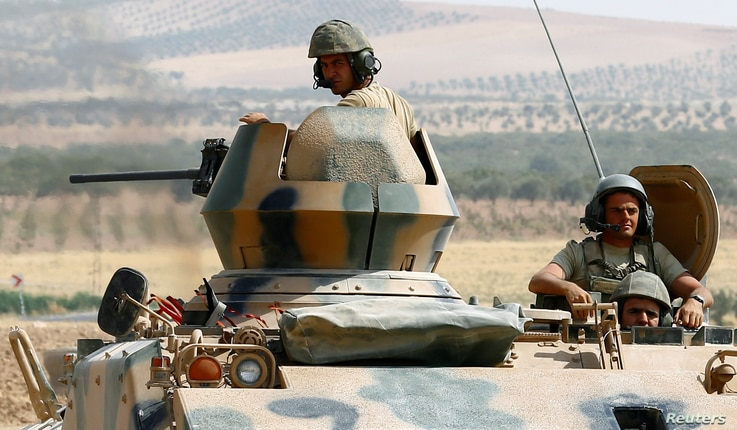 Turkish soldiers on an armoured personnel carrier escort a military convoy on a main road in Karkamis on the Turkish-Syrian border in the southeastern Gaziantep province, Turkey, Aug. 26, 2016.