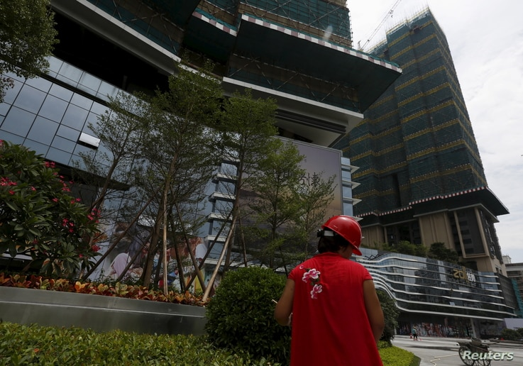 FILE - A cleaner at work outside a new luxury apartment tower under construction in the southern Chinese city of Shenzhen, Aug. 28, 2015.