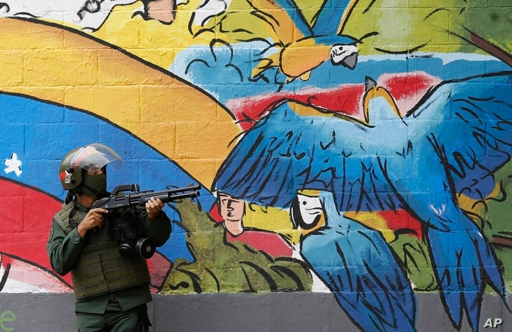 A National Guard points his weapon during clashes with anti-government demonstrations in the streets of Caracas, Venezuela.